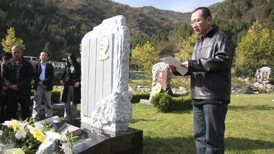 This Oct. 28, 2008 photo shows Liu Xiaobo, right, reading a letter beside the grave of Bao Zunxin, a Chinese historian and political dissident who was arrested and jailed for his role in the 1989 Tiananmen Square democracy protests in Beijing, China.